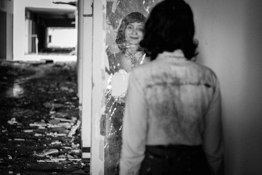 woman staring into broken mirror