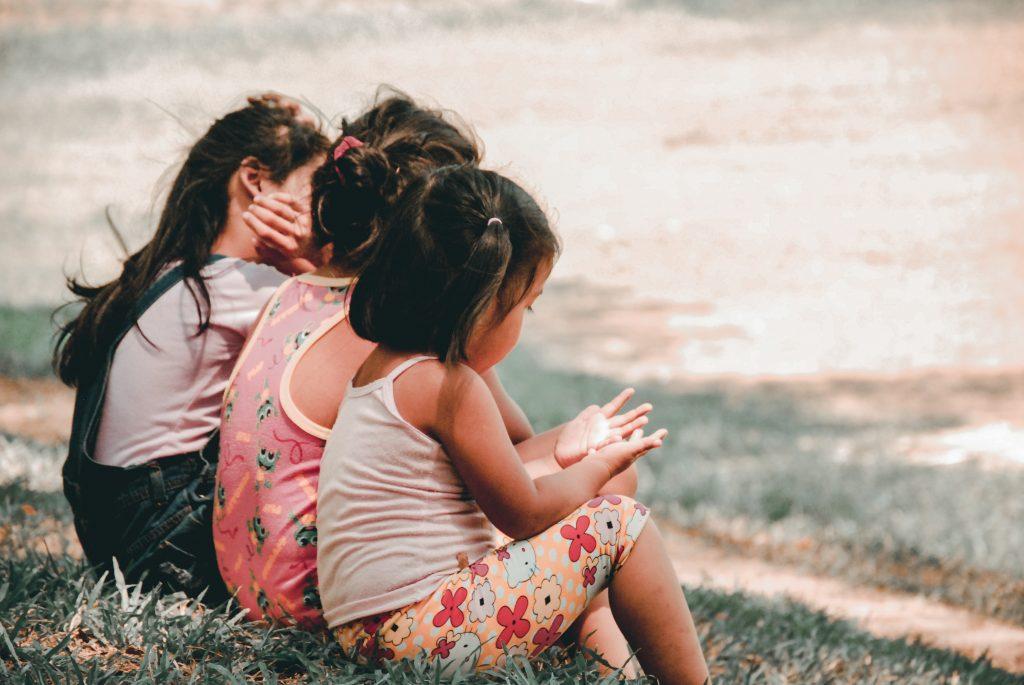three children sitting in the grass