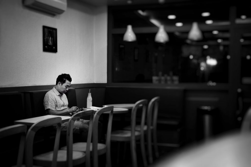 man alone at cafe looking at phone