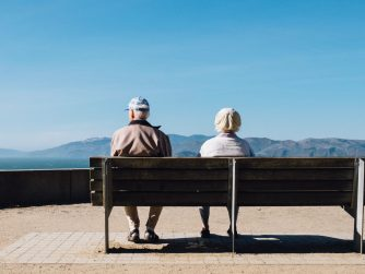 older man and woman on bench