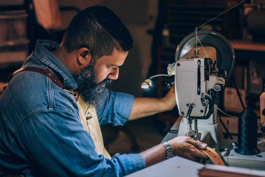 man sewing belt