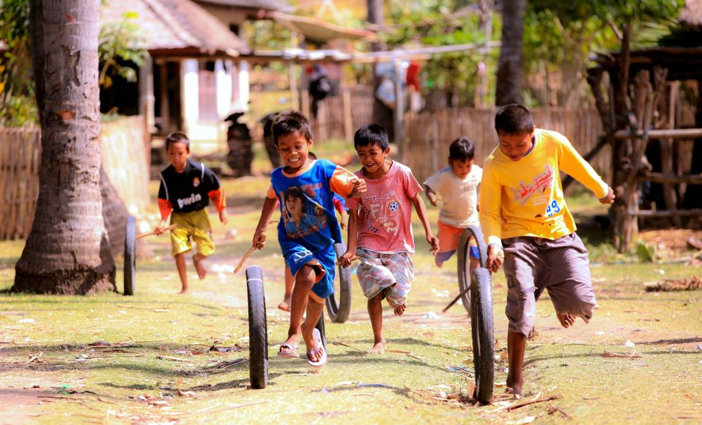 Children play with tires and sticks in Indonesia