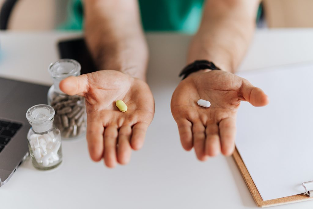 two hands offer two pills