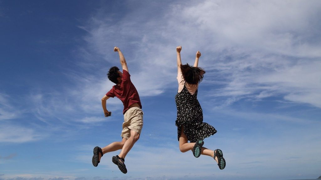 2 people jumping into the air