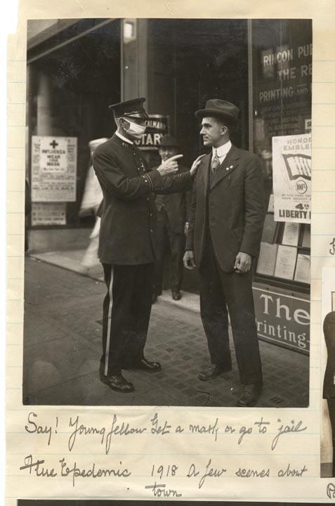 A policeman warns a man to get a flu mask;