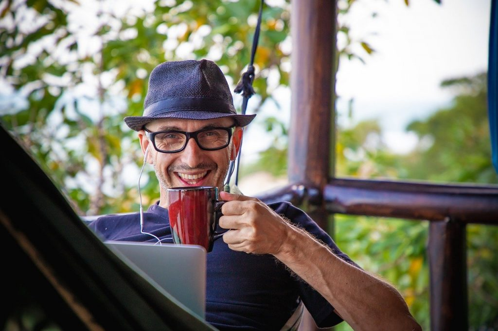 A man in a hammock uses a computer and drinks coffee