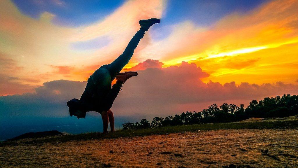 a person balances against a sunset