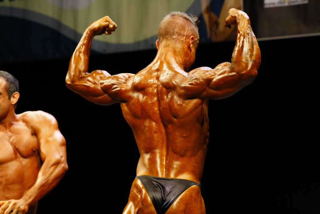A man poses at a bodybuilding competition