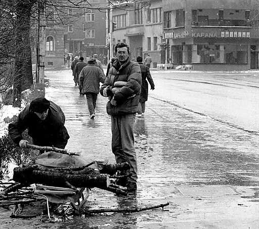 The siege of Sarajevo, 1992-1993. One man gathers firewood from branches and another man holds loaves of bread;